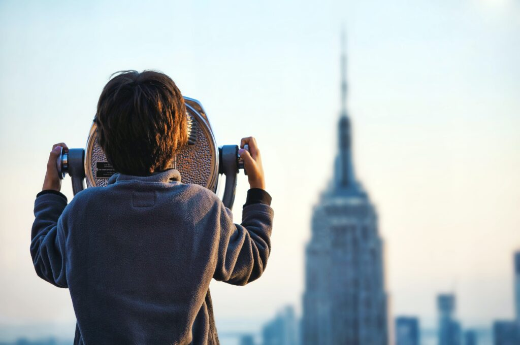 How to spot a great credit card bonus. Child looking at empire state building through fixed binocular stand
